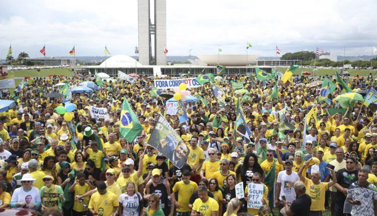 Manifestantes pró-Bolsonaro vestem camisas verde e amarelo e empunham bandeiras do Brasil e cartazes contra o PT