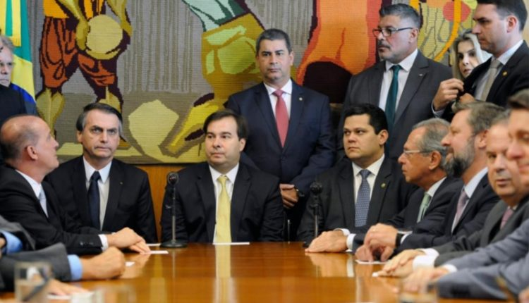 Líderes. Onyx, Bolsonaro e Maia (sentados, à esq.) dividem a cena com Alexandre Frota e Flávio Bolsonaro (em pé, à dir.)